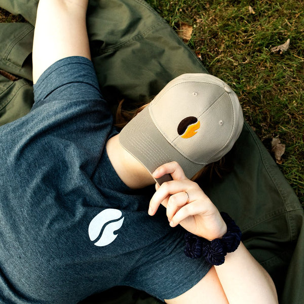 Woman laying on the ground wearing Twill FRC Bean Baseball Hat.