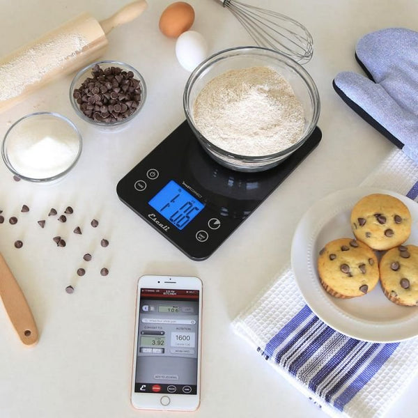 Black Escali SmartConnect Digital Kitchen Scale surrounded by various kitchen appliances and foods.