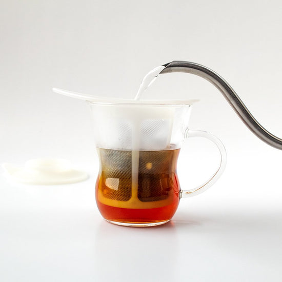 Spout pouring water into a Hario One Cup Tea Maker.