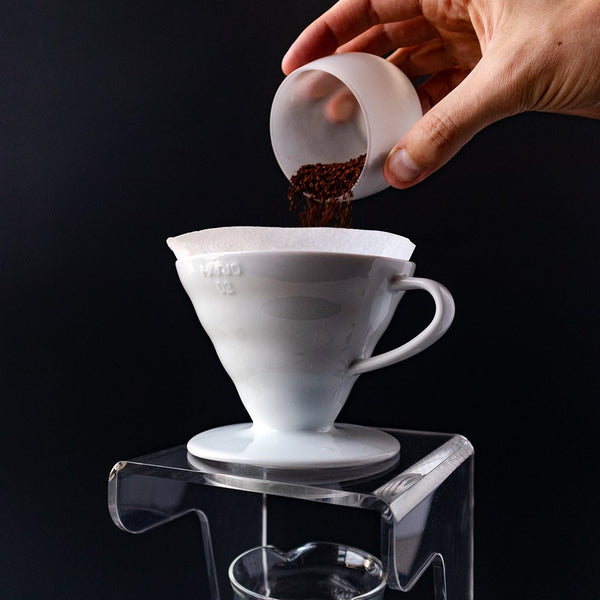 Coffee grounds being poured into a Hario V60 Ceramic Coffee Dripper.