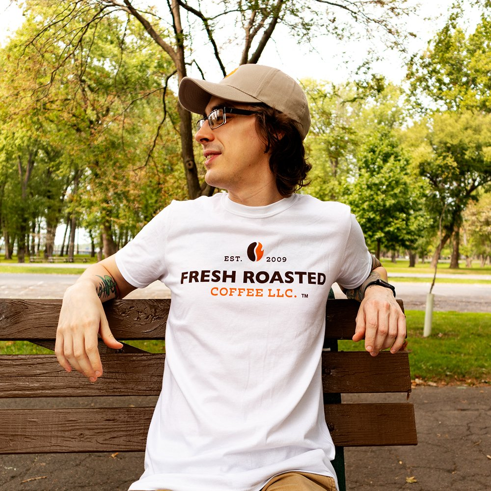 Man on bench wearing white fresh roasted coffee t shirt and khaki hat.