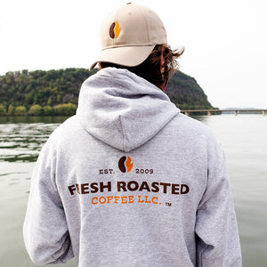 Man, back towards the camera, wearing gray Fresh Roasted coffee hoodie and khaki hat with orange and black coffee bean logo.