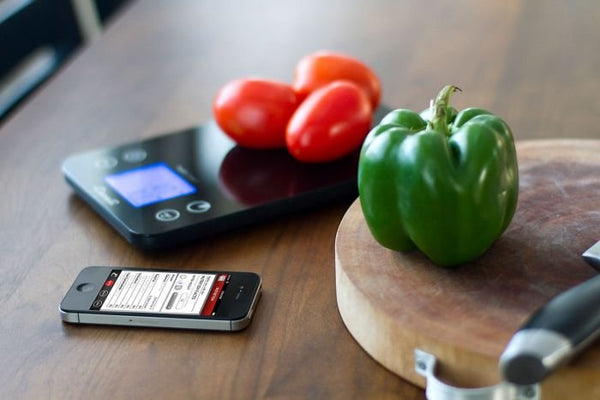 Overhead view of a black Escali SmartConnect Digital Kitchen Scale, Roma tomatoes on top, next to a green bell pepper and a phone.