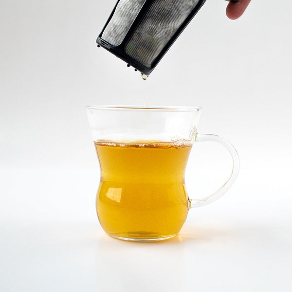 Hario One Cup Tea Maker held above a glass of fresh tea.