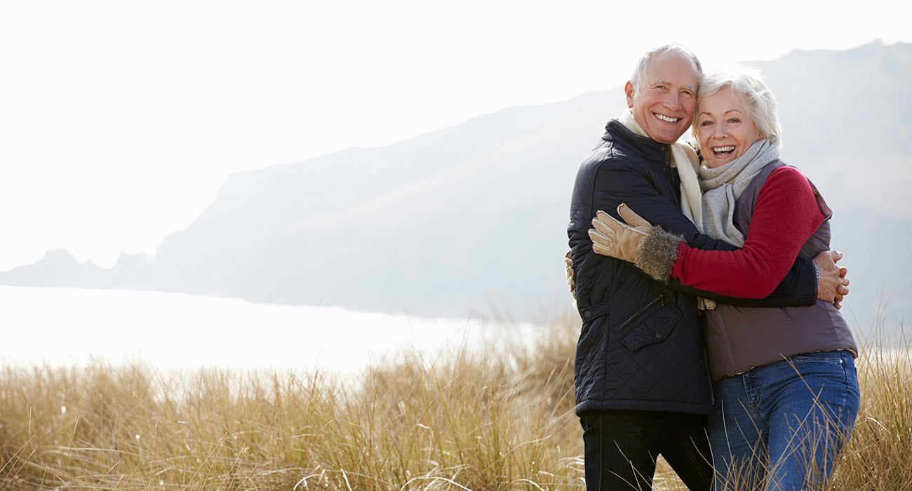 Senior couple smiling and hugging for a portrait above the sea
