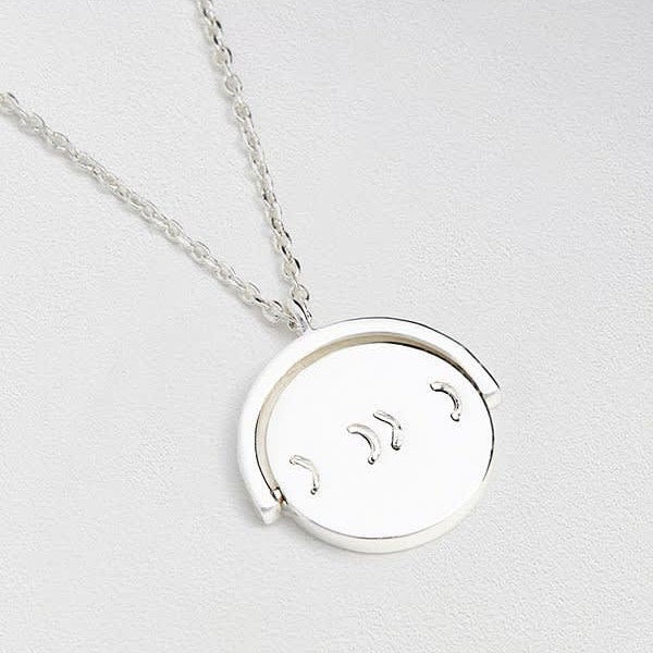 Necklace with a spinning 'XOXO' pendant in silver