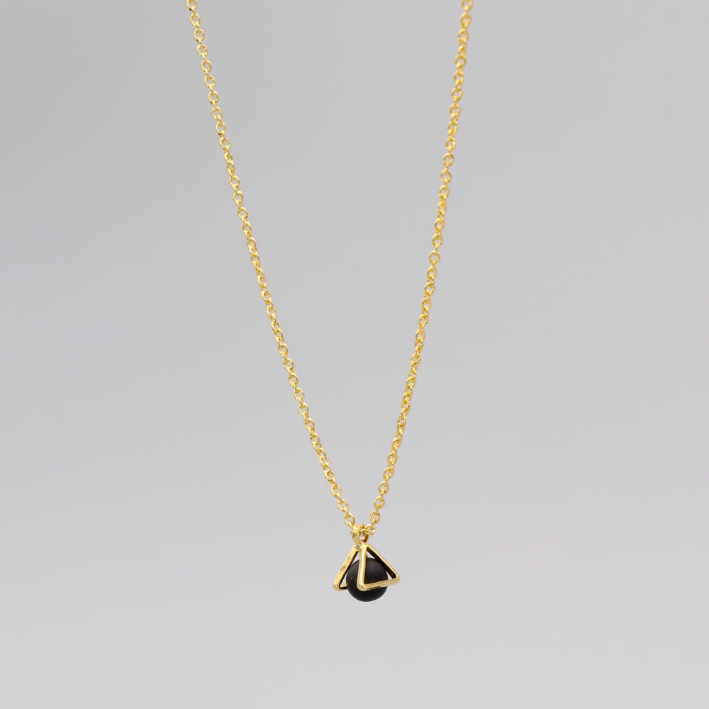 Gold necklace with a triangular caged charm