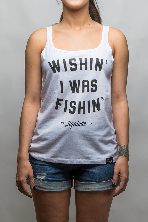 "Young woman wearing a white tank top that reads ""Wishing I was Fishing"" from fishing apparel brand, Jigalode."