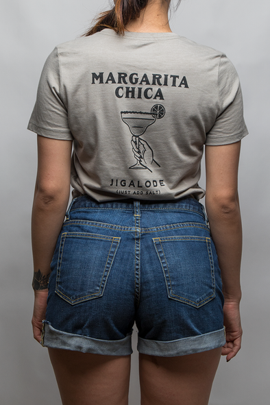 "Young woman wearing a gray t-shirt of a womans hand holding a margarita glass the shirt reads ""Margarita Chica, Jigalode (Just add salt)"". From Fishing Apparel brand, Jigalode."