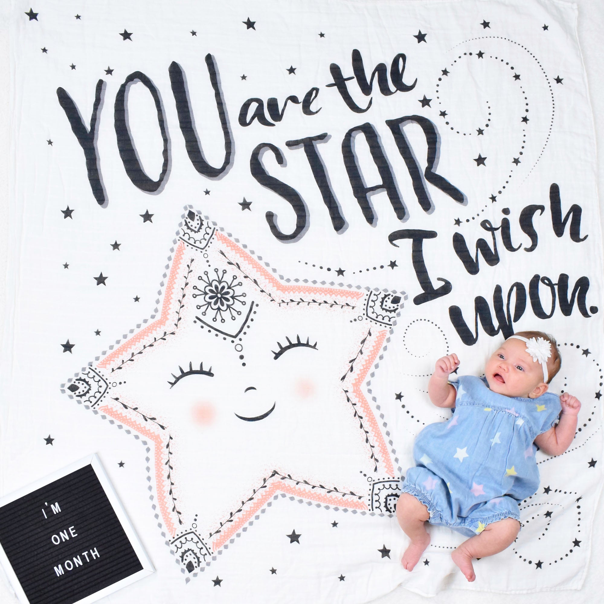 "I month old baby girl on ""You are the Star I wish upon"" Swaddle blanket used as a milestone blanket"