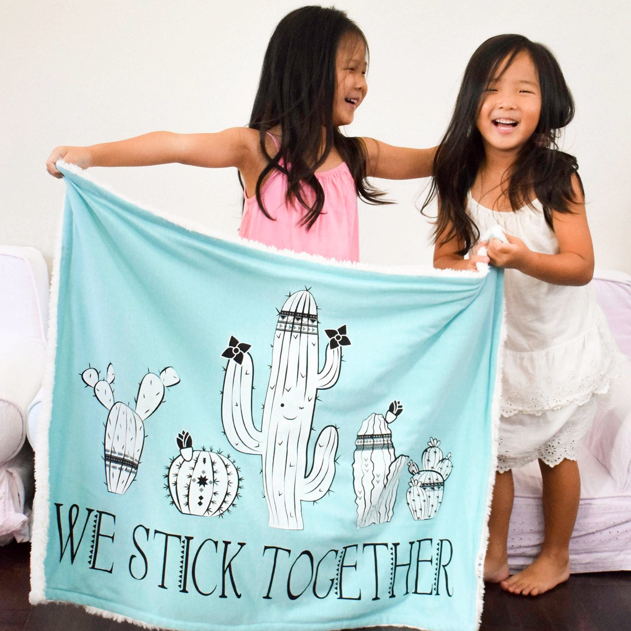 Two sister having fun with their We Stick Together Cozy Blanket