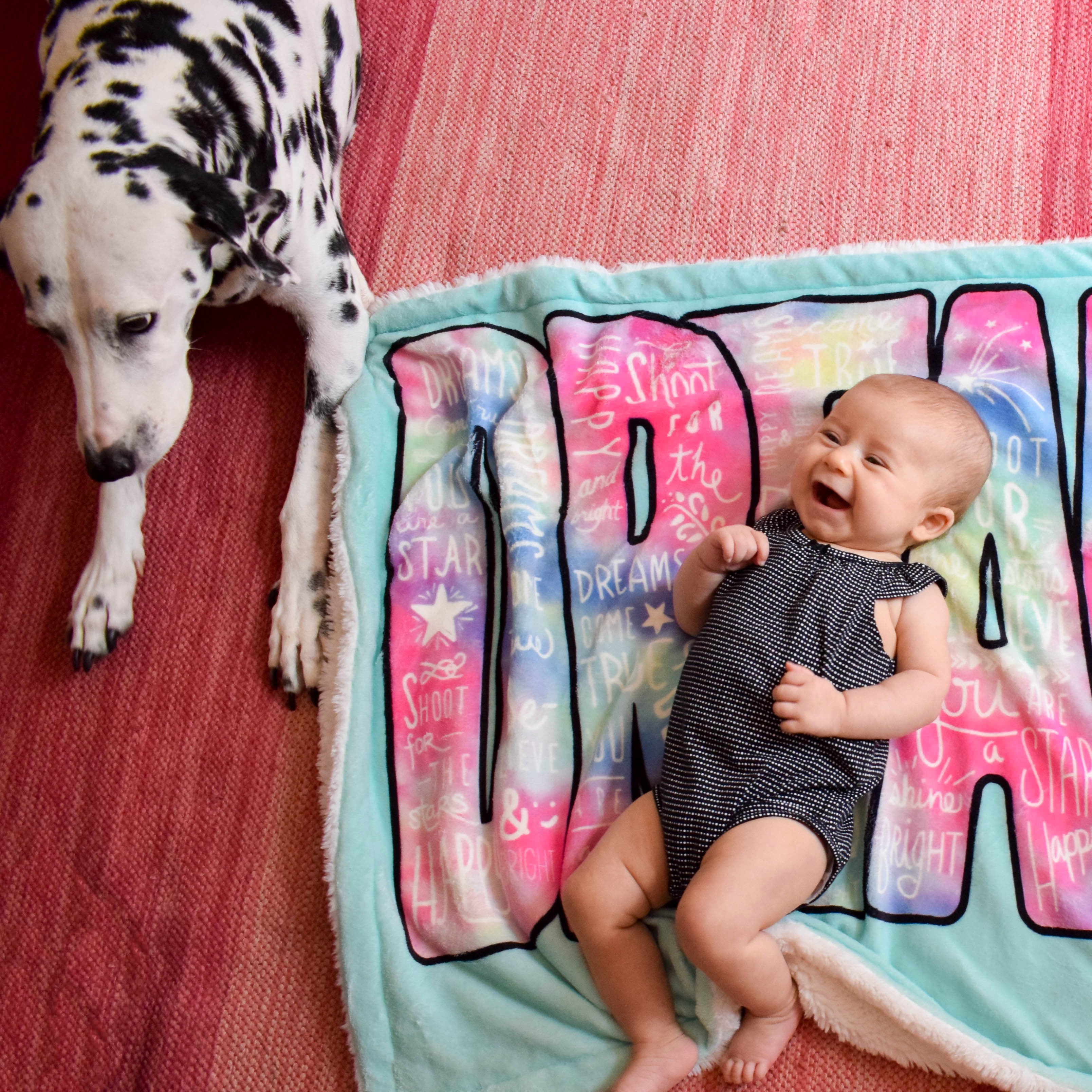 Baby Girl and Dog Laying on Dream Big Baby Blanket
