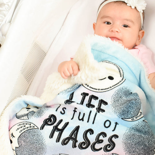 Baby girl laying down with her Life is full of Phases security mini blanket