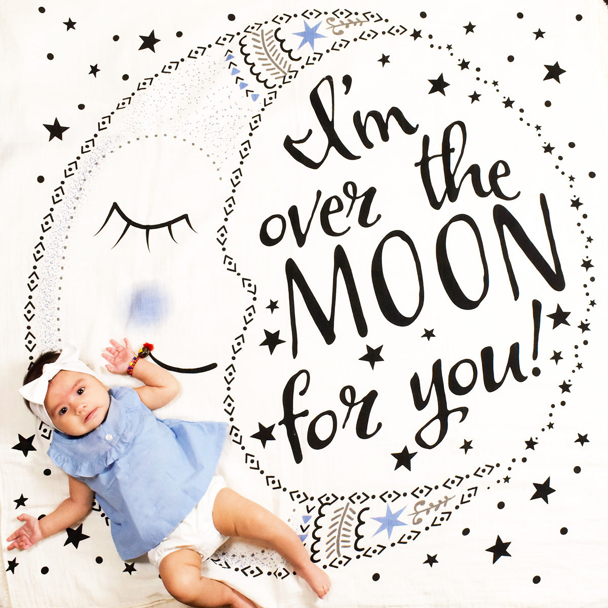 Baby girl on I'm over the Moon for you swaddle blanket