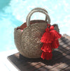 "Petite Luna ""Hibiscus Fuschia"" - Round Straw Bag with Fuschia tiered pom -poms"