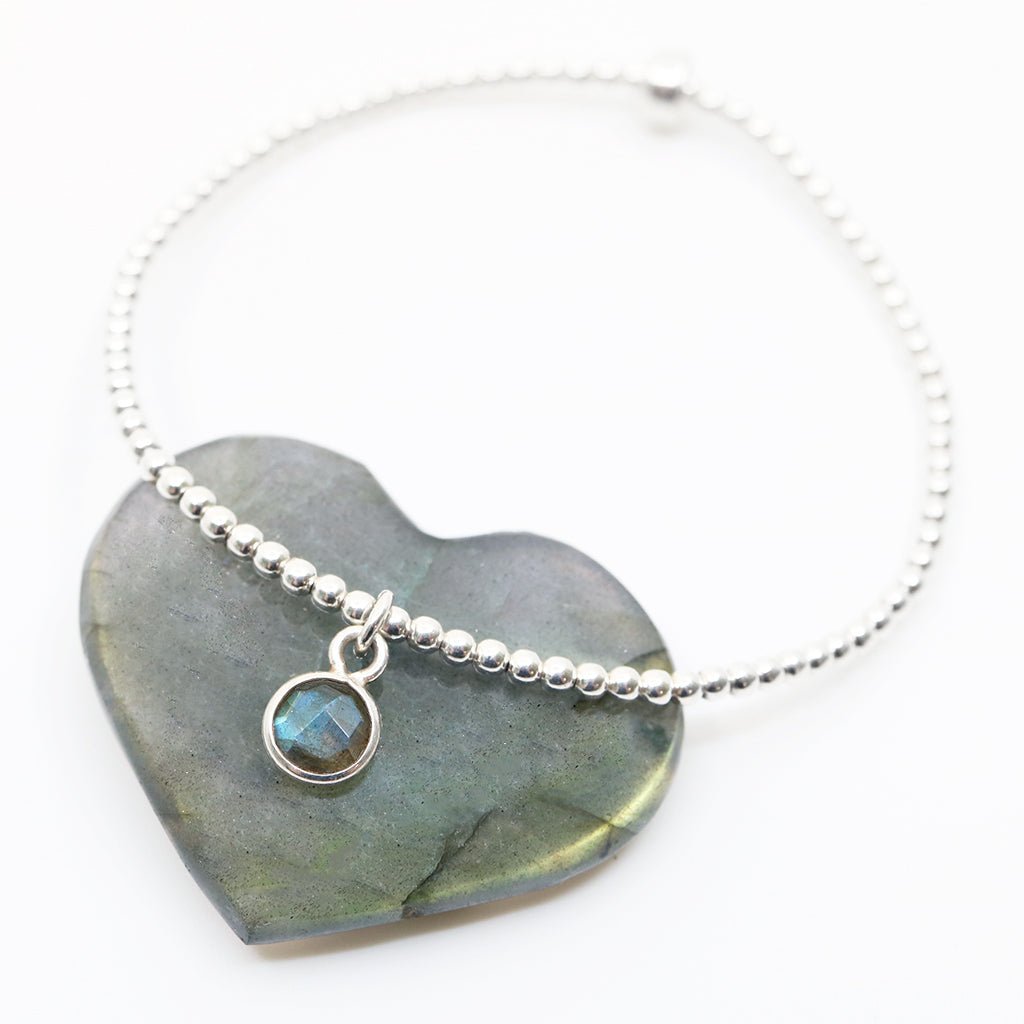 Small labradorite gemstone circle pendant encased in sterling silver dangling from a sterling silver beaded stretch bracelet and displayed on white background