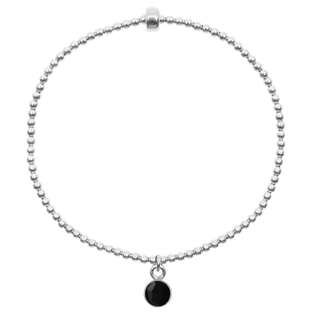 Small onyx gemstone circle pendant encased in sterling silver dangling from a sterling silver beaded stretch bracelet and displayed on white background