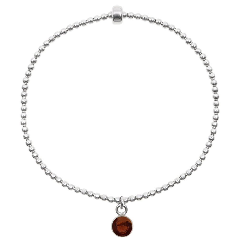 Small garnet circle pendant encased in sterling silver dangling from a sterling silver beaded stretch bracelet and displayed on white background