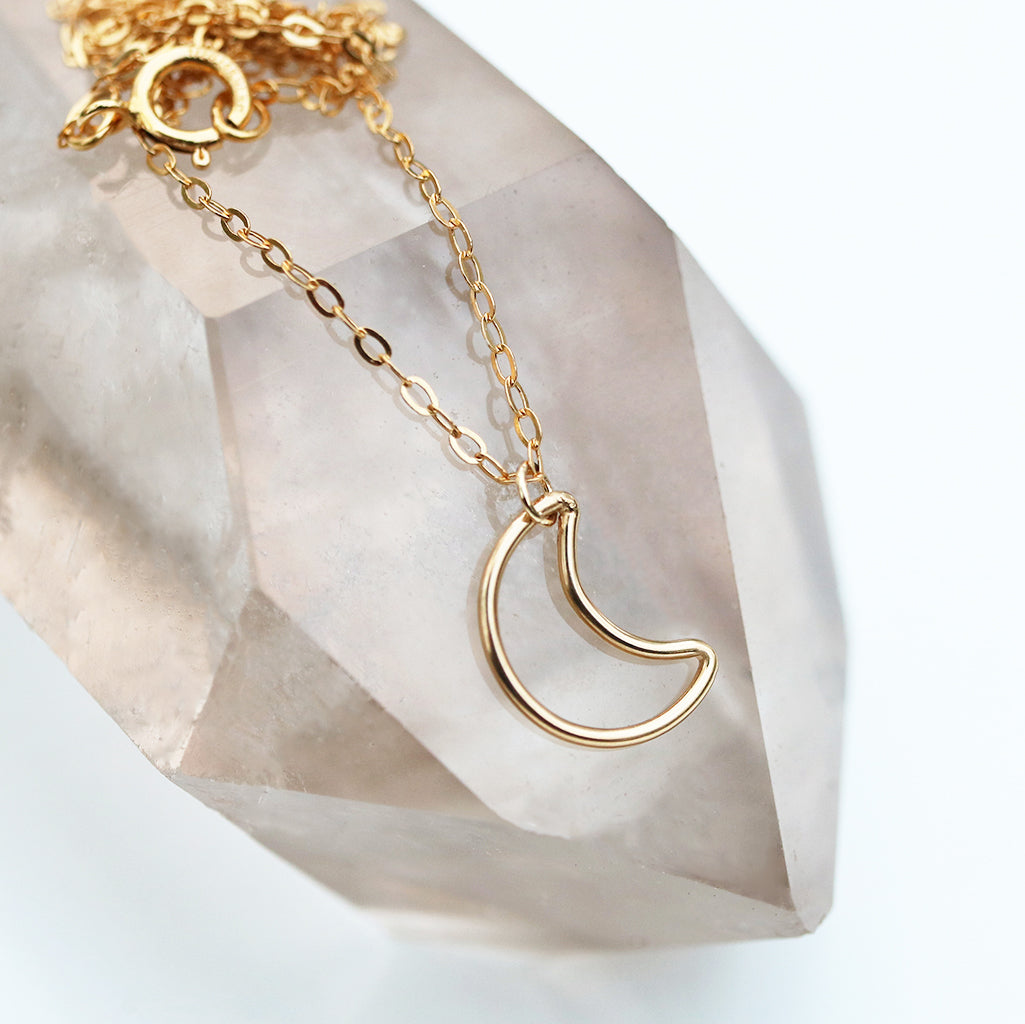 gold crescent moon pendant dangling from gold oval cable chain on white background