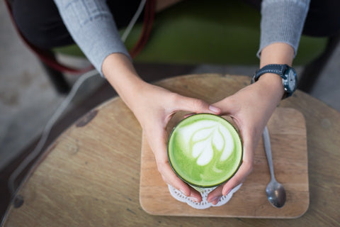 a cup of matcha green held by two hands