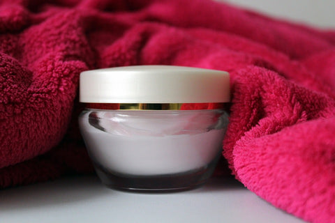 cream in a jar beside a pink towel