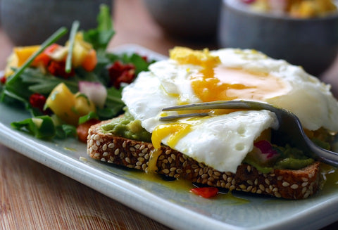 egg, wheat bread with sesame seeds and vegetable salad