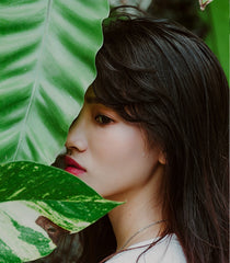 girl on side view with leaves covering part of face