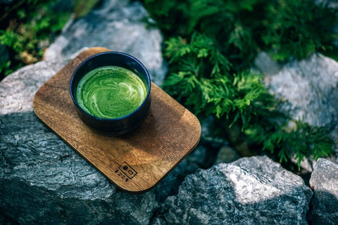matcha tea in black cup above a wooden cupboard