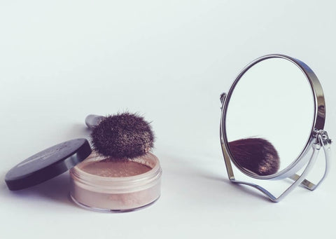 mirror with cosmetic powder and brush