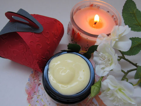 scented candle with organic cream and flower beside