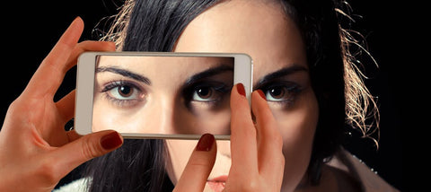 woman looking at her eyes in the mirror.