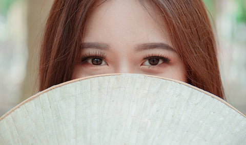 woman with fan covering the face and eye exposed
