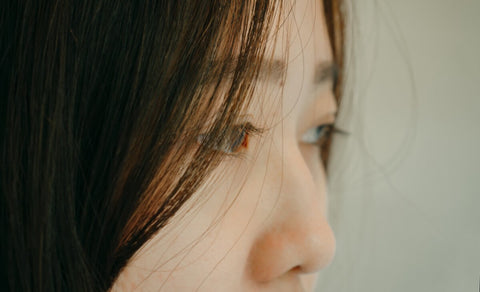 woman with straight hair and long eyelash on sideview