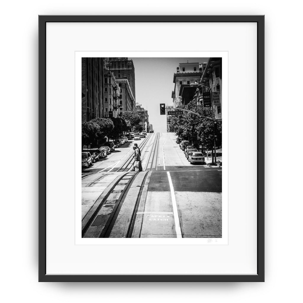 Framed version of a Black and White Photography fine art print of a typical San Fransisco Street with two people crossing the road.