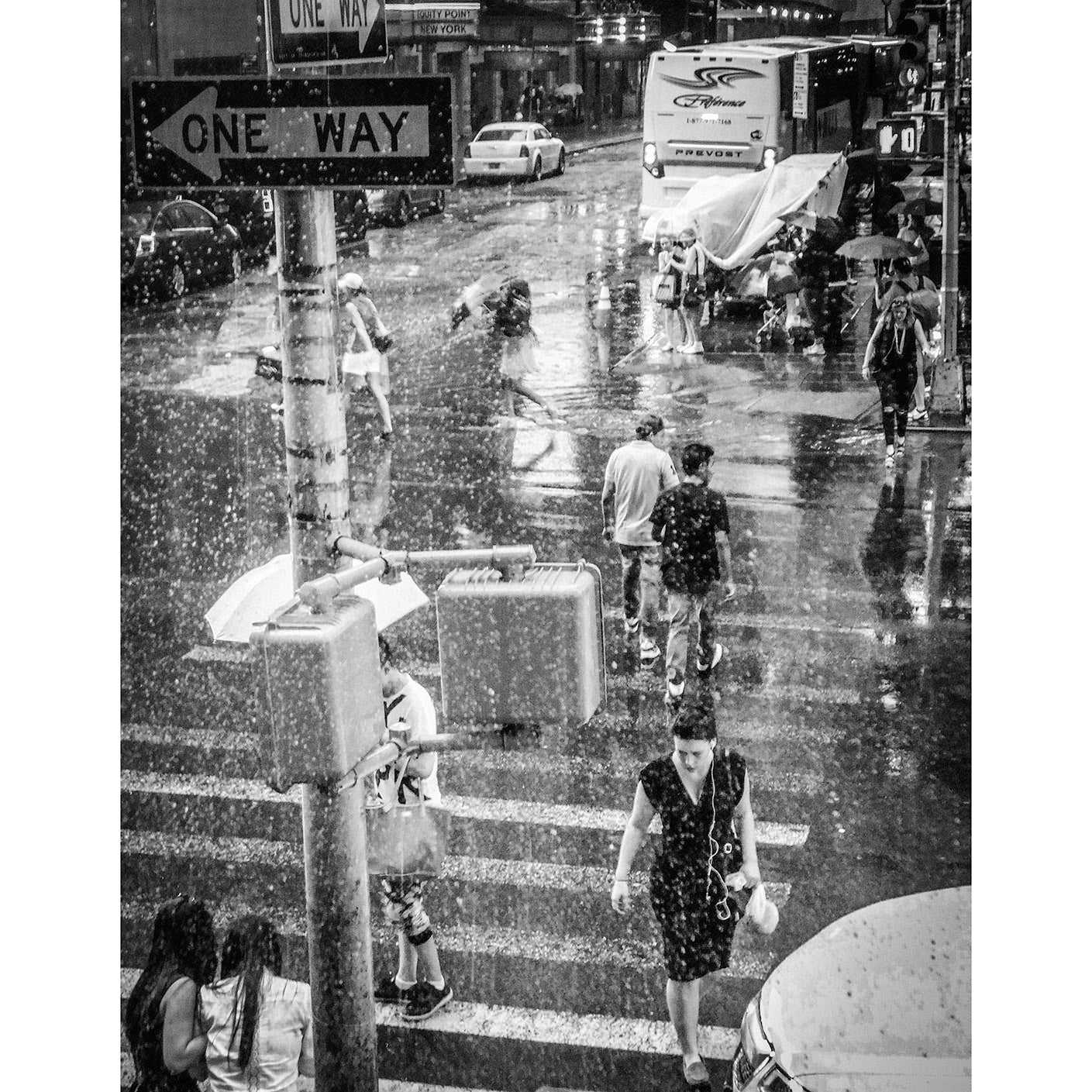 A black and white photography fine art print of a New York Street with various people crossing the road while it is raining.