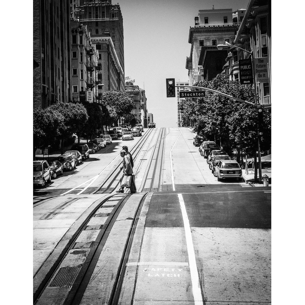 A Black and White Photography fine art print of a typical San Fransisco Street with two people crossing the road from what Phil sees.