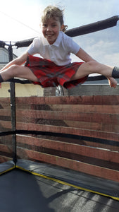 Gymnasts in action wearing tartan culottes as part of their school uniform