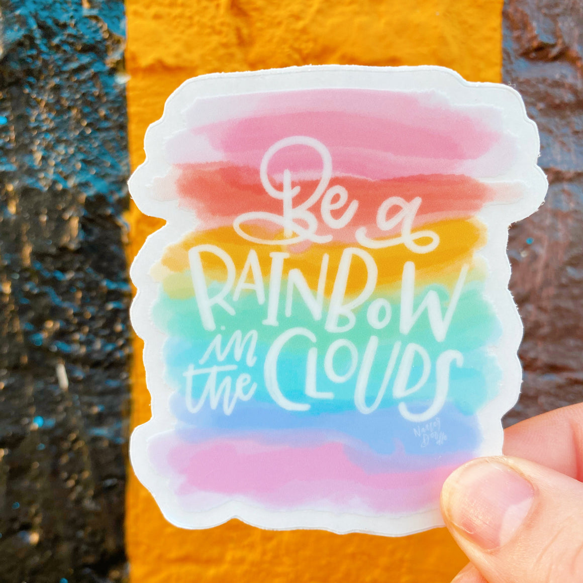 "Die cut sticker features a watercolor rainbow background and the phrase ""be a rainbow in the clouds"""
