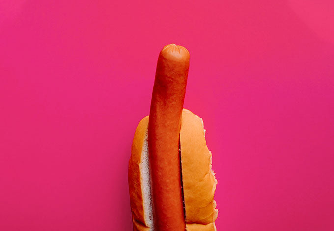 Perky hot-dog symbolizing erection from using male sex toys