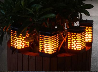 LED lanterns hanging from a bush.