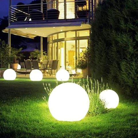 Globe shaped lights on a lawn.
