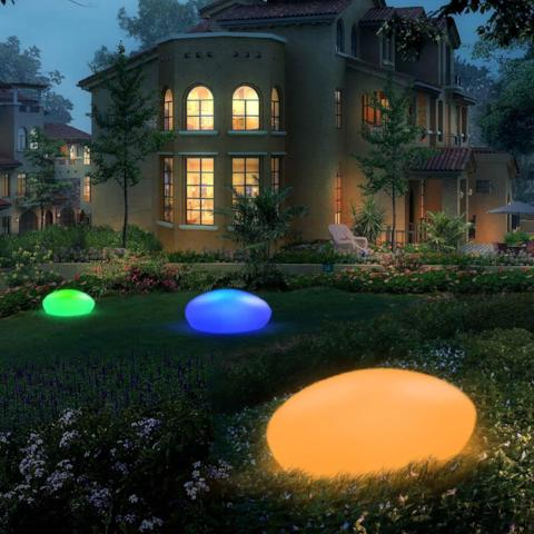 Pebble shaped LED lights on a lawn.