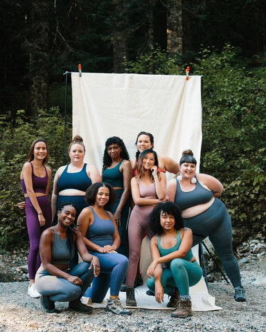 various women in gym clothes, sports bras, leggings looking at the camera