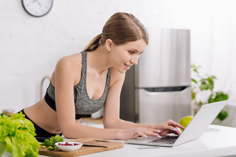 woman in activewear at home on computer