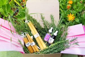 "a summer heart of fire creative ritual box in the garden contains one pair of 10"" taper candles, 2 pairs of 6"" candles, , 4 pairs of mini candles, a bottle of Molten Courage, a bottle of Safe Passage and fresh sprigs of rosemary"