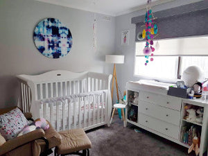 baby nursery with cot, hanging mobile, change table