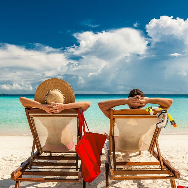 couple on sun lounges on beach holiday