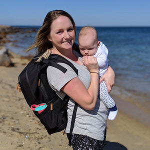 mum baby at beach with nappy backpack