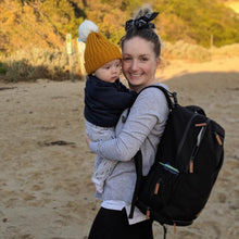 mum baby with backpack on beach