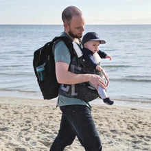 dad with baby carrier at beach